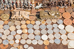 Coins, toy soldiers and tanks for sale on a flea market Stock Image