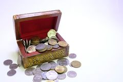 Coins in treasuary chest. Coins in treasure chest over whitw background Royalty Free Stock Image