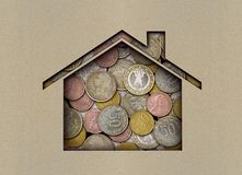 Coins under a sheet of paper with a carved house royalty free stock images