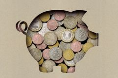 Coins under a sheet of paper with a cut out image of a pig stock photo