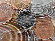 Coins under water. Coins underwater in a water pond with waves Royalty Free Stock Image