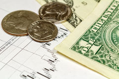 Coins with US dollars banknotes on the background of currency growth schedule Royalty Free Stock Images