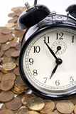 Coins and vintage black alarm clock Royalty Free Stock Images