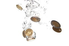 Coins in water. Money in water with bubbles on white background Royalty Free Stock Photography
