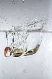 Coins in water Stock Photos