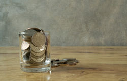 Coins in water glass. Coin in glass and other coins on wood table royalty free stock photography