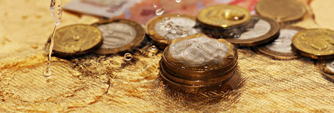 Coins and water splashes, business object royalty free stock photo