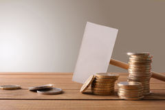 Coins on wooden table with banner and brown background Royalty Free Stock Photo
