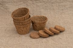 Coir plant pots and compressed compost on hessian. Environmentally friendly spring gardening. Coir plant pots and compressed compost on hessian. Eco-friendly royalty free stock photo