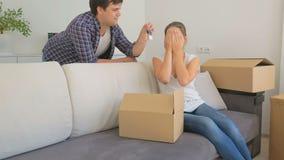 Coisas da embalagem da jovem mulher em umas caixas O homem entra na sala e em dar suas chaves da casa nova filme