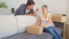 Coisas da embalagem da jovem mulher em umas caixas O homem entra na sala e em dar suas chaves da casa nova video estoque