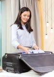 Coisas da embalagem da mulher de negócios na mala de viagem Imagem de Stock
