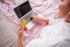 Coisas de compra da menina no Internet em casa fotografia de stock