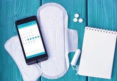 Coisas e calendário da menstruação no smartphone Imagem de Stock Royalty Free