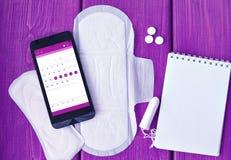 Coisas e calendário da menstruação no smartphone Imagem de Stock