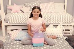 Coisas Girlish A criança da menina senta-se perto da cama com saco ou da trouxa em seu quarto A criança prepara-se para ir para a fotografia de stock
