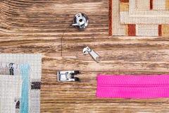 Coisas para a máquina de costura e as partes de tela colorida, em um fundo de madeira escuro Fotografia de Stock