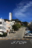 Coit Tower,San Francisco. A steeply-sloping residential street scene in San Francisco, with the Coit Tower in the background Royalty Free Stock Photography