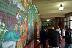Coit Tower in San Francisco - CA. SAN FRANCISCO - MAY 18 2015:Visitors and mural at Coit Tower lobby in San Francisco California.Coit Tower listed as San Royalty Free Stock Photos