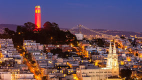 Coit Tower and St. Peter and Paul Church. View of Coit Tower and St. Peter and Paul church at night, from Lombard street. Coit tower is lit red and gold in honor Stock Image