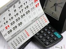 Cojín, calculadora en las hojas del calendario Fotos de archivo