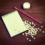 Cojín de escritura y las píldoras Fotografía de archivo