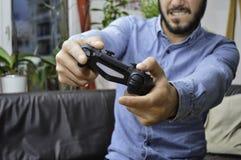 Cojín hermoso joven nervioso del juego de la tenencia del hombre y el jugar a los videojuegos imagen de archivo libre de regalías