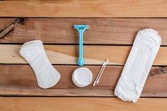 Cojines femeninos de los productos de higiene, esponjas de algodón y una maquinilla de afeitar en la madera natural imagen de archivo libre de regalías