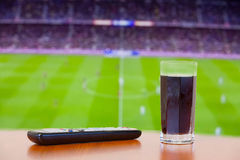 Coke fizzy drink, tv remote on a table. Watching football (socce Stock Images