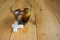 Cola with ice and lemon with sugar cube. Coke with ice and lemon on wood Stock Images
