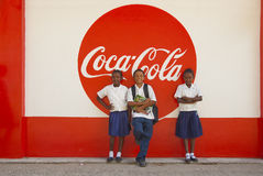 The coke kids. Three black school kids on the island of Roatan ( Honduras ) posing in front of a coca cola wall painted sign Stock Photo