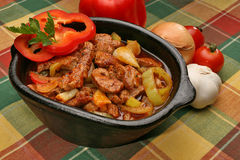 Coked pork meat with peppers. In a clay vessel Royalty Free Stock Photos