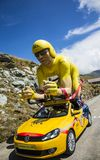 LCL Yellow Cyclist Mascot in Alps - Tour de France 2015. Col de la Croix de Fer, France - 25 July 2015: The famous LCL Yellow cyclist mascot on the road to the Stock Photos