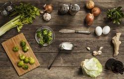 Col, tomates, ajo y cebollas en la tabla de madera vieja Imagen de archivo