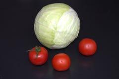 Col y tres tomates en un fondo oscuro Foto de archivo
