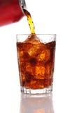 Cola che versa da una latta in un vetro. fotografie stock