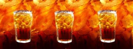 Cola con los cubos de hielo en fondo abstraído de los colas Foto de archivo