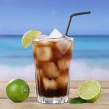Cola or Cuba Libre cocktail on the beach. Cola or Cuba Libre cocktail drink in glass with ice cubes on the beach Stock Photos