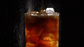 Cola de colada con el primer de los cubos de hielo en fondo negro almacen de video