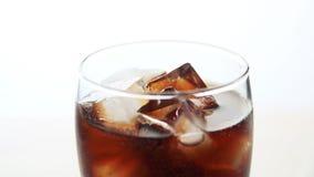 Cola de colada en el vidrio con hielo en el fondo blanco almacen de video