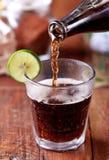 Cola de derramamento a um vidro Imagens de Stock Royalty Free