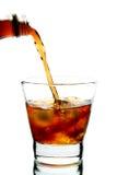 A cola derramou no vidro com gelo Imagens de Stock Royalty Free