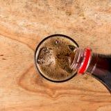 Cola di versamento nel vetro sulla tavola di legno Fotografie Stock Libere da Diritti