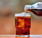 Cola di versamento in un vetro di ghiaccio immagini stock