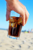 Cola drink on the beach. Closeup of the hand of a young man with a glass with refreshing cola drink on the beach Royalty Free Stock Photo