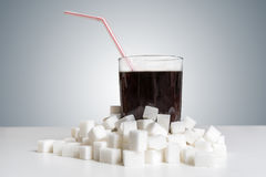 Cola drink in glass and many sugar cubes around. Unhealthy eating concept.  royalty free stock photos