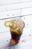 Cola drink with lemon lime in glass on white table Stock Image
