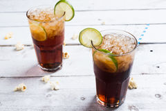 Cola drink with lemon lime in glass on white table Royalty Free Stock Image