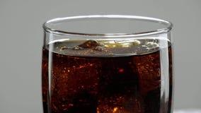 Cola fría de restauración con los cubos de hielo en la cámara lenta almacen de video