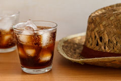 Cola. Glass of cola with iced cube and hat on summer time royalty free stock image